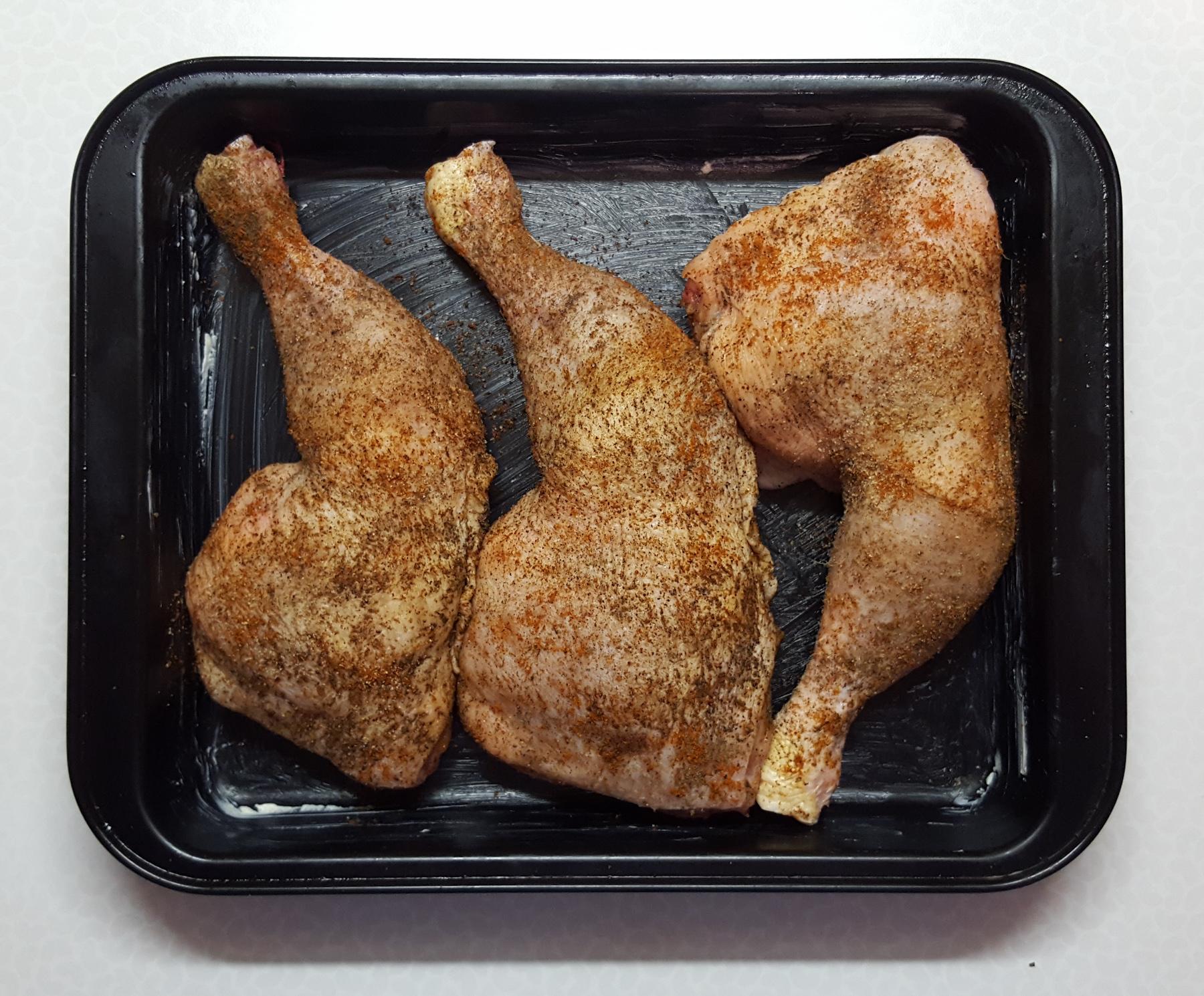 Hähnchenschenkel, gewürzt mit Salz, Pfeffer, Paprika- und Knoblauchpulver