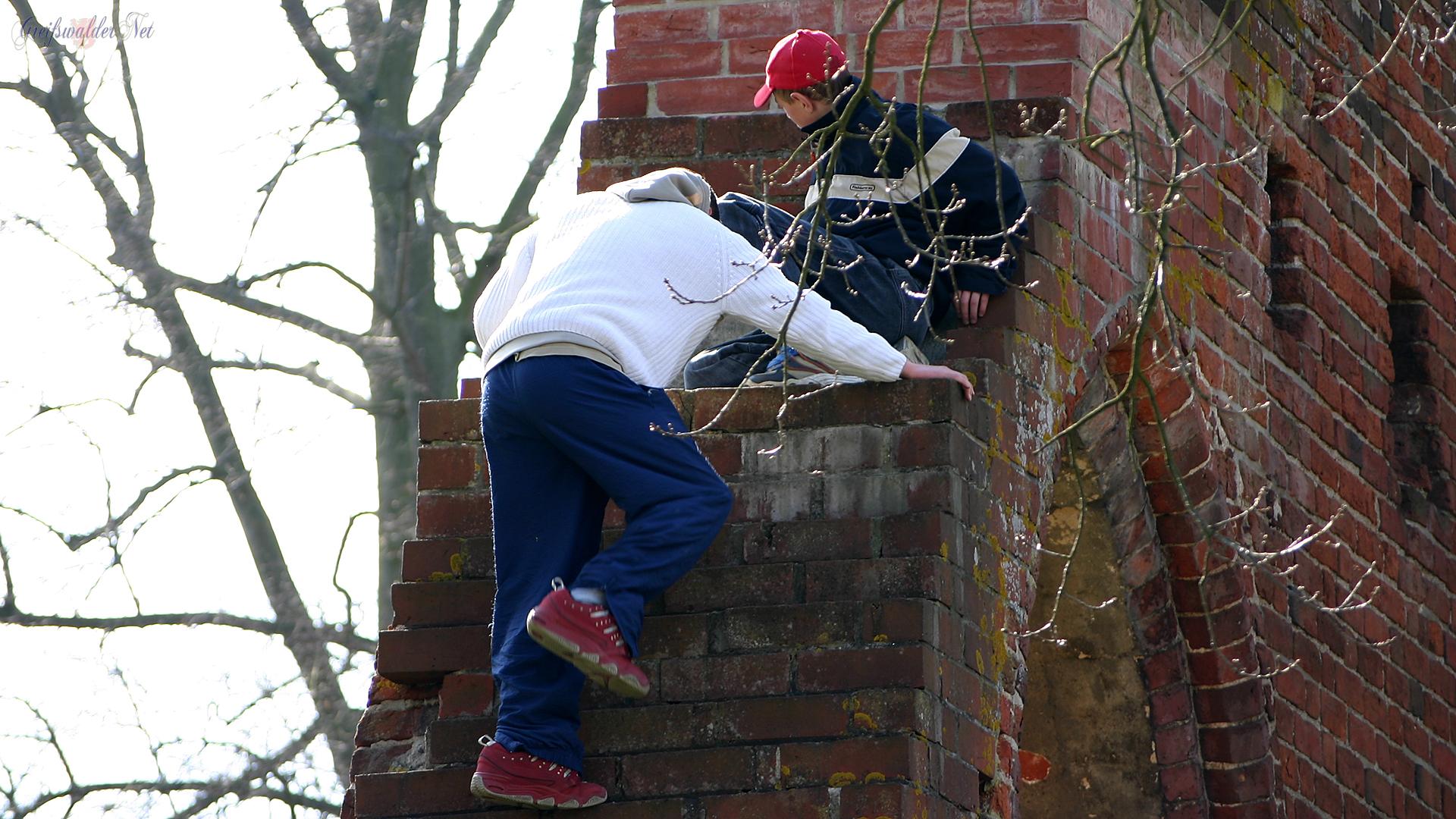 Jugendliche klettern auf der Klosterruine in Greifswald-Eldena