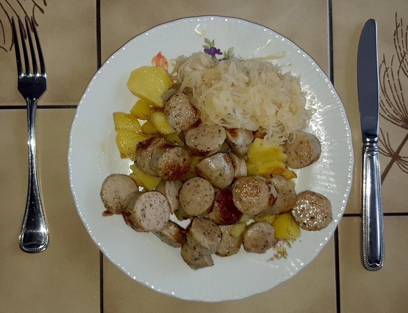 Mittagessen: Bratwurst mit Bratkartoffeln und Sauerkraut