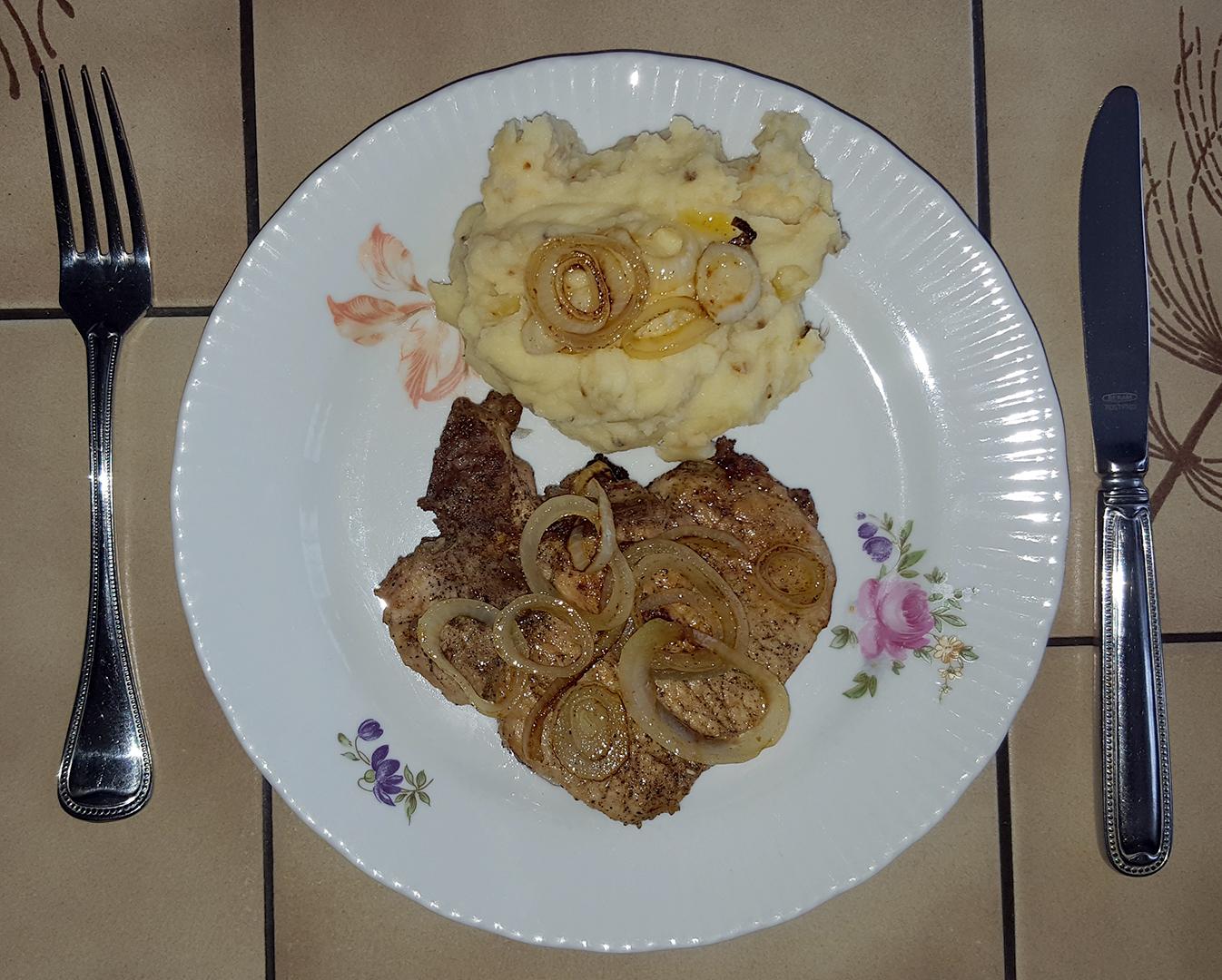 Schweinekotelett mit Kartoffelpüree und Zwiebelringe